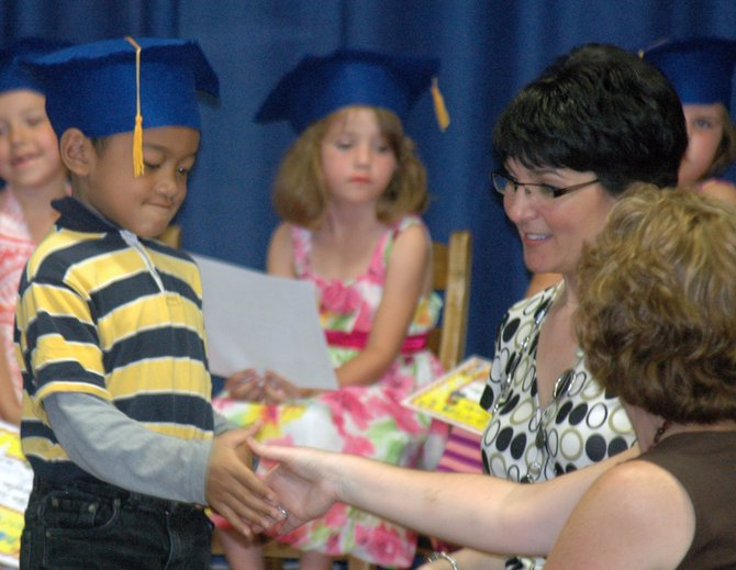 Eseloni Malafu accepts his kindergarten graduation certificate from Westport Central School principal Michelle Friedman and kindergarten teacher Julie Bisselle. Westport was one of the top local schools in the U.S. News and World Report rankings for institutions in New York State.