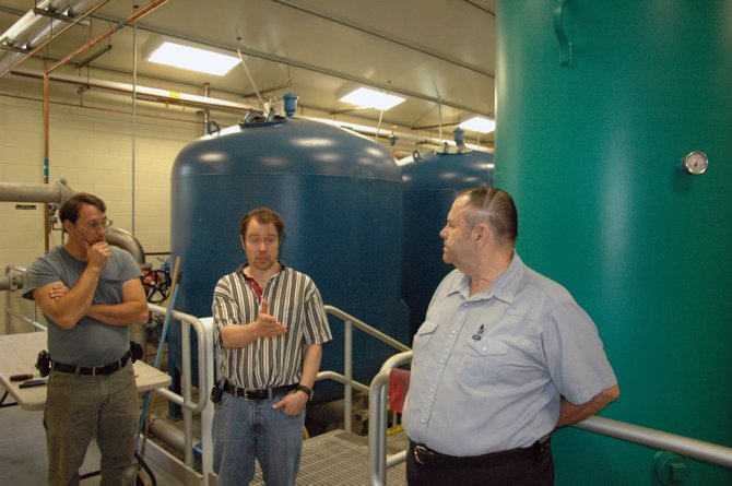 Port Kent Water Treatment Facility manager Dave Winter, left, and Chesterfield Supervisor Gerald Morrow, right, listen to AES engineer Todd Hodgson talk about the filtering system at the new plant.