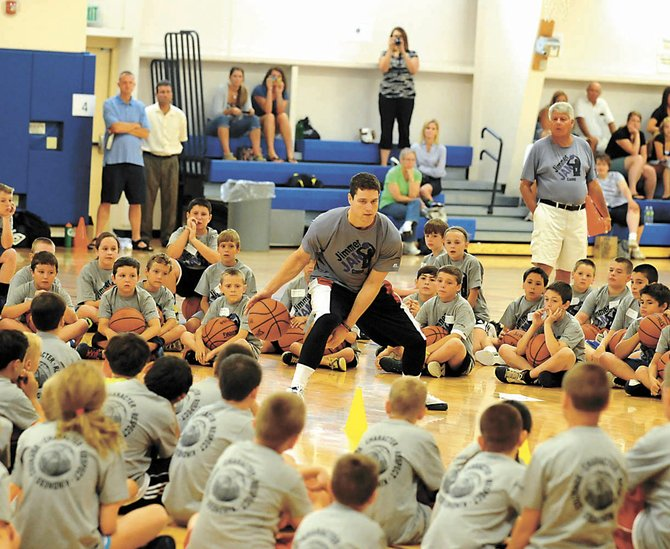 "Sacramento Kings guard and Glens Falls native Jimmer Fredette, center, demonstrates his dribbling skills to a group of young players on the opening day of his ""Jimmer Jam"" camp Thursday at the Saratoga Springs Recreation Center. Three hundred kids are attending the three-day camp."