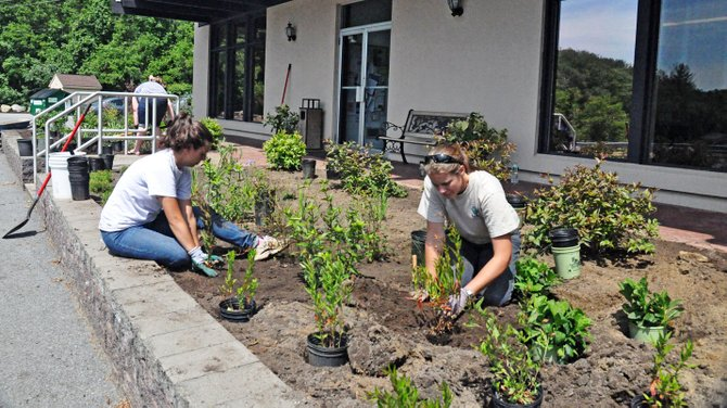  Jill Trunko (left) and Emily DeBolt help install native plants for a new demonstration garden at the  Lake George town hall.
