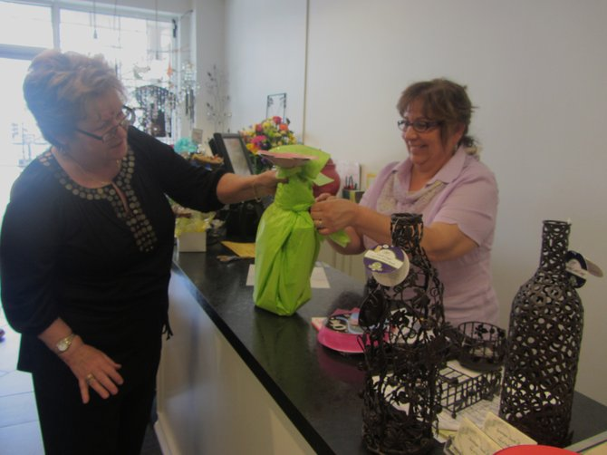 Saratoga South Boutique's Joan Rello and Kathy Zelker wrapping a gift for a customer.