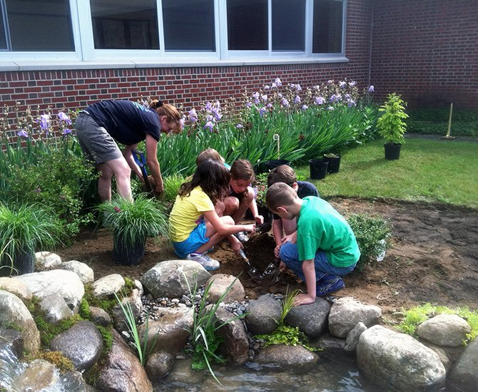 Jefferson second-grade students prepare to plant a butterfly friendly Columbine in the new garden at the school's courtyard.
