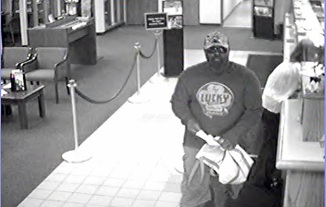 The suspect, shown here on bank surveillance video, is described as about 6 feet tall, between 220 and 250 pounds and black. He may have used a fake goatee and mustache and was wearing dark glasses, khaki shorts, a dark sweatshirt with the word lucky on the front, white sneakers and a light-colored baseball cap.
