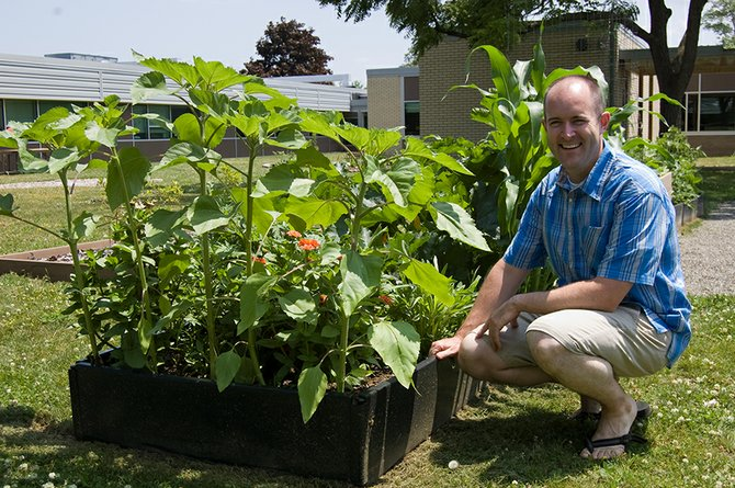 "Niskayuna High School biology teacher Christopher Jennings on Friday, June 22, kneels next to a garden bed blossoming with plant-life at the new ""outdoor science classroom."""