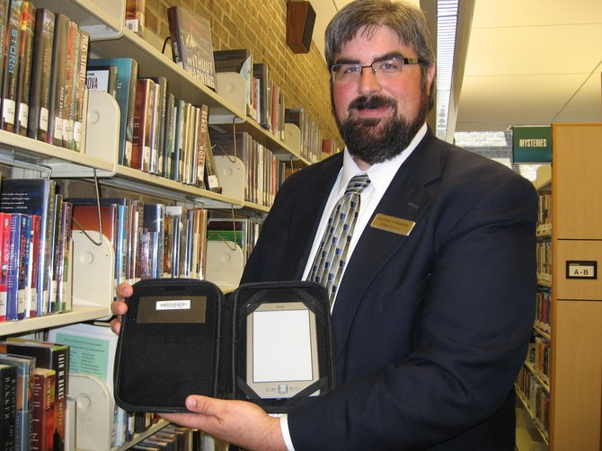 Geoffrey Kirkpatrick, director of the Bethlehem Public Library shows off a Kindle reader available to library patrons. The electronic readers are pre-loaded with titles from the library's collection. They are not able to download other e-book titles, however.