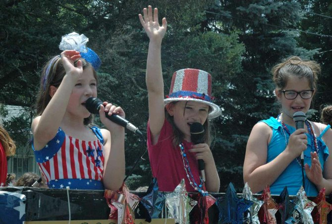 "Katie Rondeau, Emily Wesley and Camryn Lincoln sing ""Grand Ole Flag"" as part of the Rockn Mtn Singers during the Jay parade."