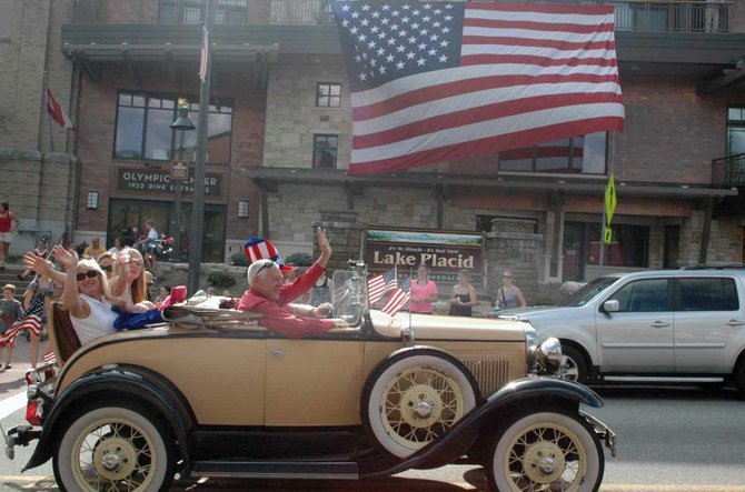 A classic car passes the American Flag at the Lake Placid Convention Center during the Fourth of July parade.
