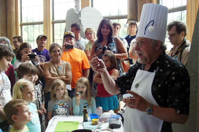 Insect chef David George Gordon holds up a chili and lime spiced grasshopper as an interested crowd waits for a sample. 