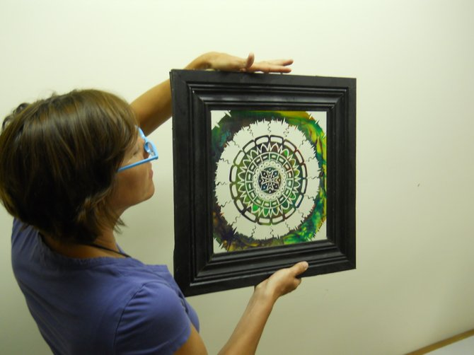 Stony Creek Library Director Lisa Bartow hangs a painted glass etching by local artist Eric Fleming as she prepares for an ambitious art show at the library. The library is holding an artists reception for the exhibit from 7 to 9 p.m. Thursday July 12, and accomplished musician Travis Bartow and his band is scheduled to provide entertainment.