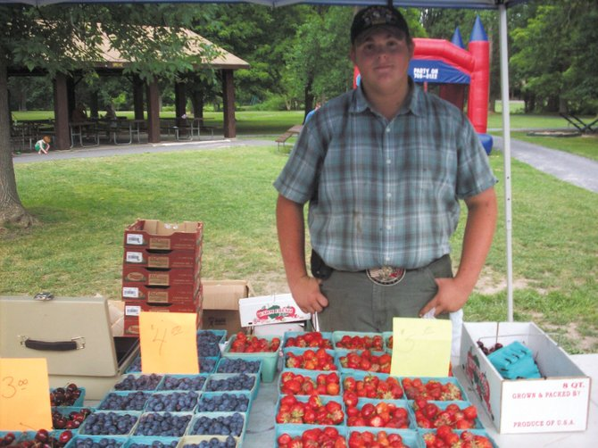 Travis North, of Annas Flowers and Vegetables, stands among a variety of produce, including strawberries, blueberries and squash, at the Marcellus Open Air Market.
