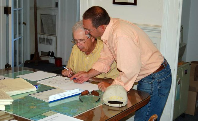 North Elba Town Supervisor Roby Politi, left, goes over some agenda items with Councilman Derek Doty prior to the Town Board's July 10 meeting at the Town House in Saranac Lake.