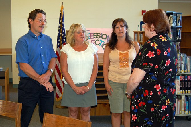 Saranac Lake Central School Board Clerk Chris Fransen, far right, swears in the recently elected members of the board on Wednesday, July 11 at the Petrova School library. From left are Miles Van Nortwick, Katie Fischer and Deb Lennon.