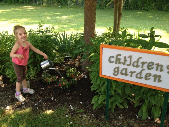 Abigail Hansen, 3, helps water the newly dedicated Children's Garden.