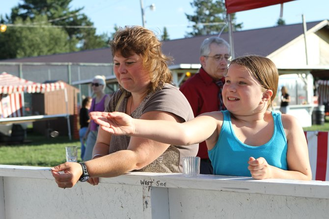 Venena Kennedy and her daughter Sierra pitch pennies at a midway booth at the 2011 Smoke Eaters&#39; Jamboree. This year&#39;s Jamboree is to be held Saturday July 27 and Sunday July 28.  Officials of the Warrensburg Fire Company, which sponsors the event, are now seeking donations of goods and services from area citizens and businesses to be sold at their auction held on the secpnd day of the carnival-like event.