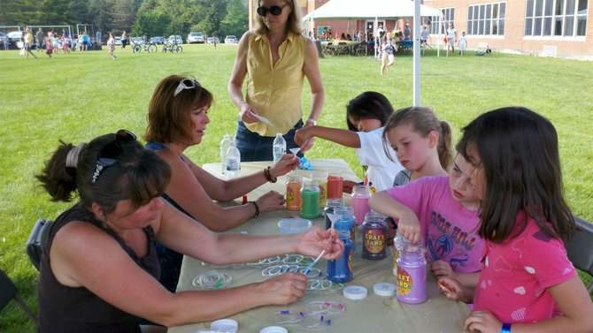 Burton Street Elementary School Principal Mary-Ann MacIntosh, left center, and Debbie Richer, left, assist young students at the sand art table during the Burton Street Elementary School End of the Year Carnival on June 21.
