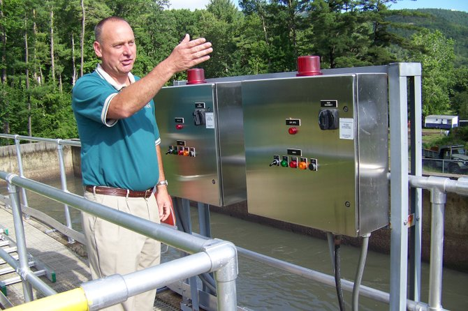 Standing at controls to a primary processing station  recently at the Lake George sewer treatment plant, village wastewater supervisor Tim Shudt explains upgrades that are proposed to boost the purity of the plant's outflows.