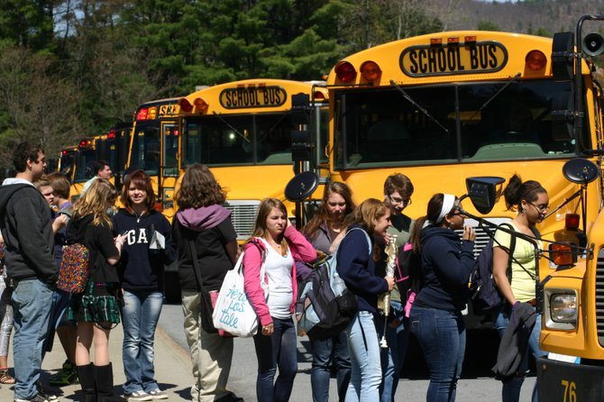 Students line up to board buses on a fall day in 2011 in front of Warrensburg High School.