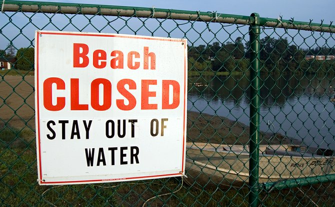 A sign posted to the fence around the Collins Park beach informs visitors the swimming area is closed. Village officials closed the beach for the entire 2012 season because visibility levels did not meet state requirements.