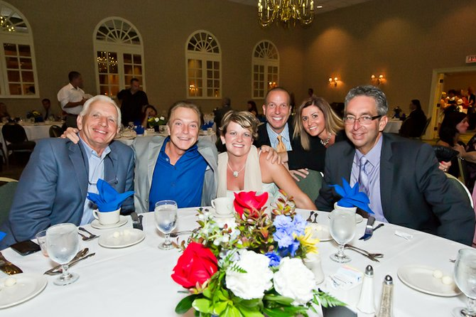 Gala Chairpersons Gary Contessa (far right) and his wife Jennifer (center, seated) celebrating with friends during last year's gala. Photo by Cathy Duffy and TR Laz.