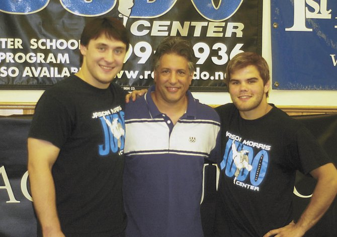 United States Olympic judo team members Kyle Vashkulat, left, and Nick Delpopolo, right, stand with their club coach, former Olympian Jason Morris, at Sundays sendoff party at Morris judo center in Glenville. Vashkulat and Delpopolo left Tuesday for the start of the Olympic games in London. 