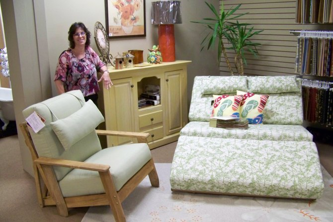 Kelly Irish, proprietor of Bear Cupboard, poses with several pieces of transportable, reclinable furniture that she offers in her home furnishings store which was once located in Warrensburg but is now situated on Glen St. in Queensbury