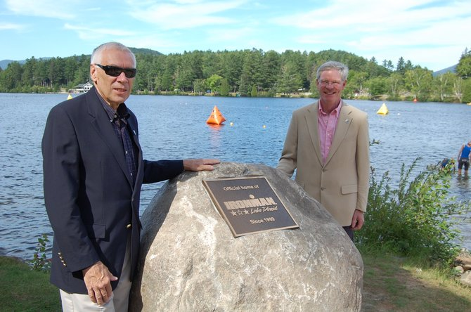 Lake Placid Mayor Craig Randall and village Trustee Art Devlin stand next the Ironman Monument dedicated on July 20 at Mirror Lake.