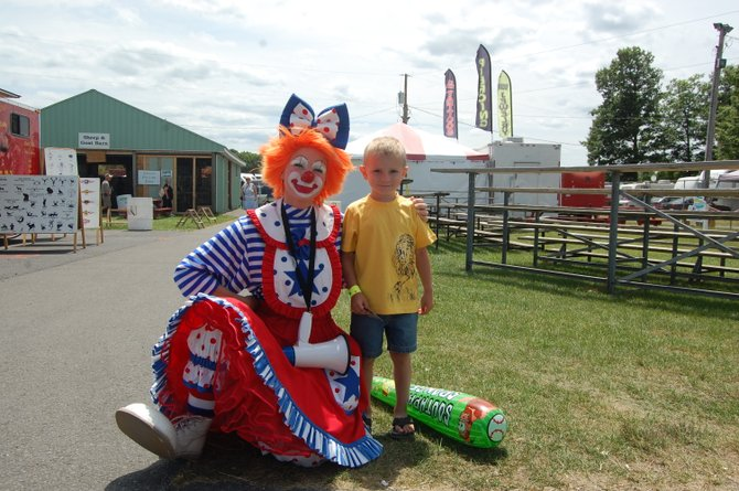 Karsen Colby hangs out with a clown before going to see the horses at the Clinton County Fair.