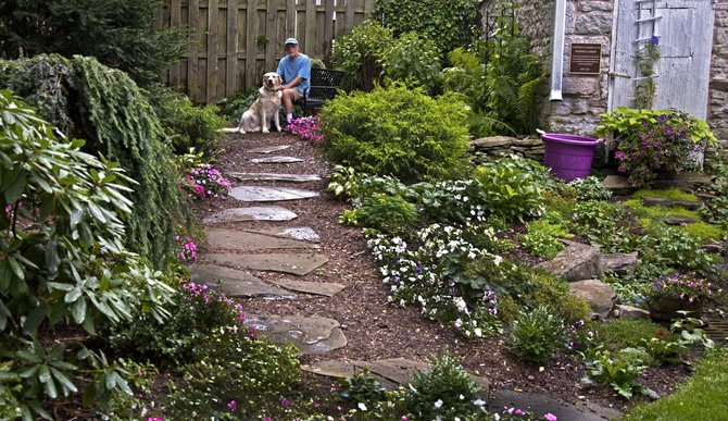Chris Nevison and BoBear sit atop the memorial garden out behind the Cazenovia Public Library. Together with his wife Barbara Wells, a member of the Cazenovia Garden Club, the couple has restructured the garden using local plants and accents.