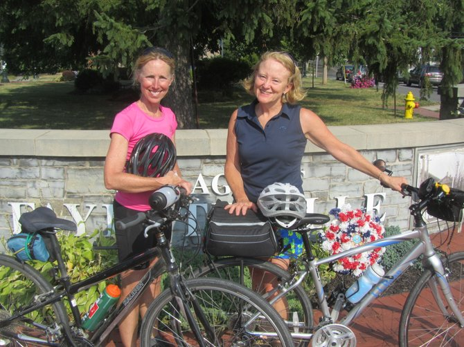 Anne Stack (left) and Robin Hodgkin, 1972 Fayetteville-Manlius High School graduates, take a break from biking across the state in the heart of Fayetteville Tuesday. They're making the trip to celebrate their 40th high school reunion.