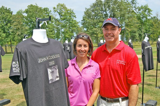 Jennifer Langlois and her husband, Jason, of Chazy, stand by a shirt that memorializes Jennifer's father, John Coolidge, who passed away in 2002 after fighting ALS.
