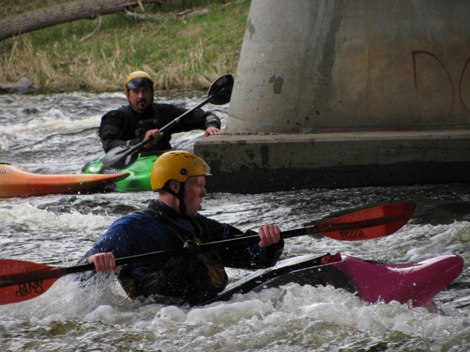 Ryan Ward works the current in the Saranac River while instructor Steve Maynard looks on. Both are supporters of a local kayak park.