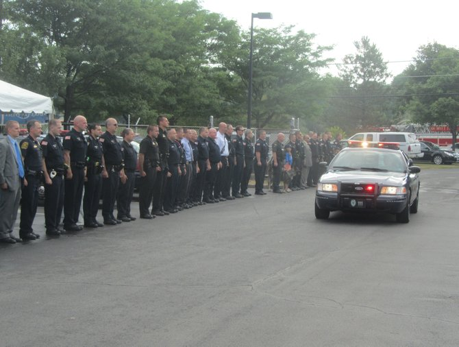 The DeWitt Police Department stands at attention as Ashton Fox arrives in a police cruiser.
