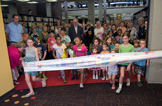 Children run through a hand-drawn banner, left, to check out the new 6,700-square-foot Children's Wing at the Central Library Branch in downtown Schenectady on Monday, July 30.