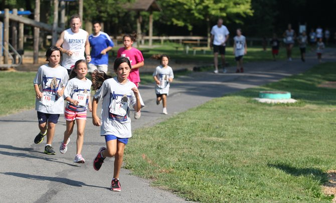Abigail Place, 10, of Jamesville, leads a pack in the one mile youth race during the third annual Bryan Place Memorial Manlius Mile and 5k Saturday at Mill Run Park in Manlius. Abigail is the daughter of Bryan Place, who died in 2010.