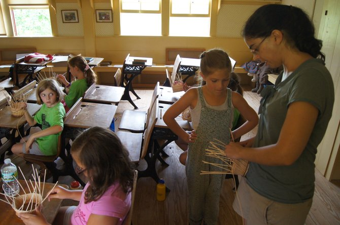 Kathleen Emerson, right, assists a student of the Rippleton Schoolhouse Summer Camp with her basket-weaving project on Aug. 1. The day camp has run for eight years, educating children of life in the 1800s through fun activities.