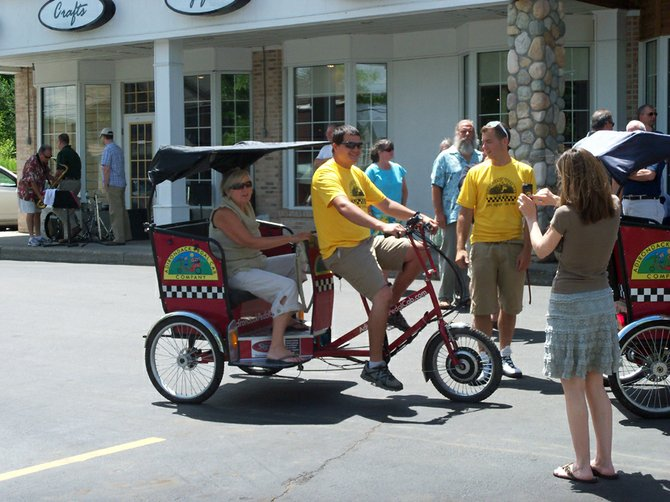 Adirondack Pedal Cab Company drivers stop at The Exchange in North Creek during the Gore Mountain Region Chamber of Commerce's Main Street ribbon-cutting celebration on June 30.