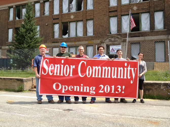 Jack Harrison, Scott Hasso, Joe Vigna, Eli Schwartzberg, Gregory Vigna, and Leah Harner of Stonebrook Properties display the banner before it's put up the former Willsboro Central School building.
