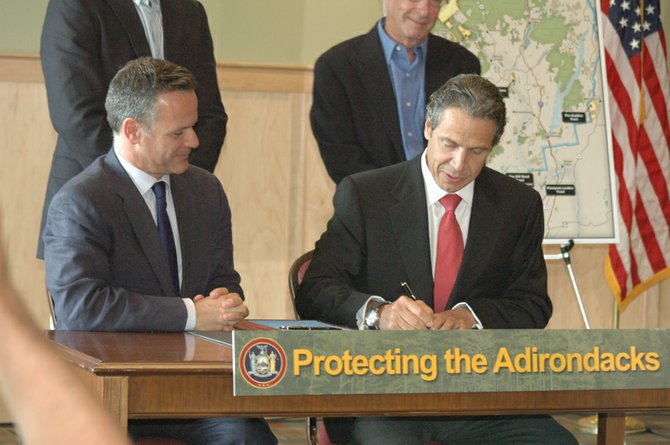 The Nature Conservancys Bill Ulfelder and Gov. Andrew Cuomo sign off on the land deal to transfer 63,000 of former Finch Pruyn land to the state.