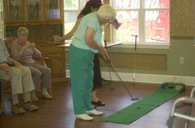 Beacon Pointe resident Audrey Crawford putts during the golf competition at the memory care center's Olympics Thursday, Aug. 2. The Clifton Park facility created several Olympic-themed events for its residents, including an opening ceremony.