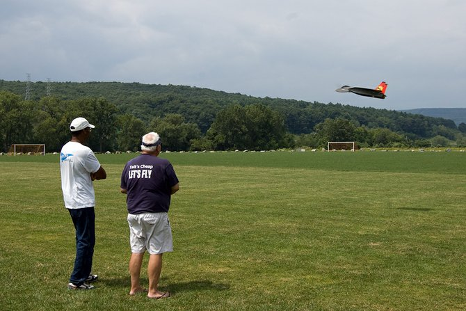 "Dave Garwood, right, flies his electric RC plane at Maalwyck Park on Sunday, Aug. 5, during the ""Fun Fly"" event as Wayne Roberts stands by and watches."