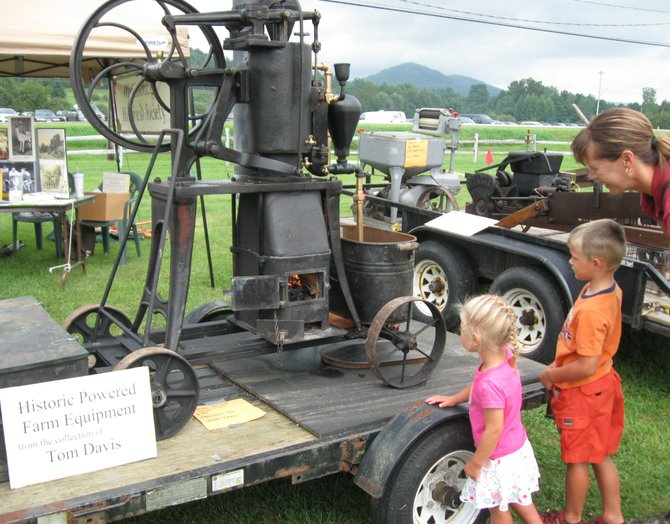 Sadie and Travis Burnett and their mother Jodi watch an antique hot-air water pump operate at the Warren County Heritage Festival held in August. Tom Davis owns the wood-fired 1886 machine, and he will be hosting a public expo of his collection of antique machinery the morning of Saturday Oct. 13 at his barn in Diamond Point — see article for details.