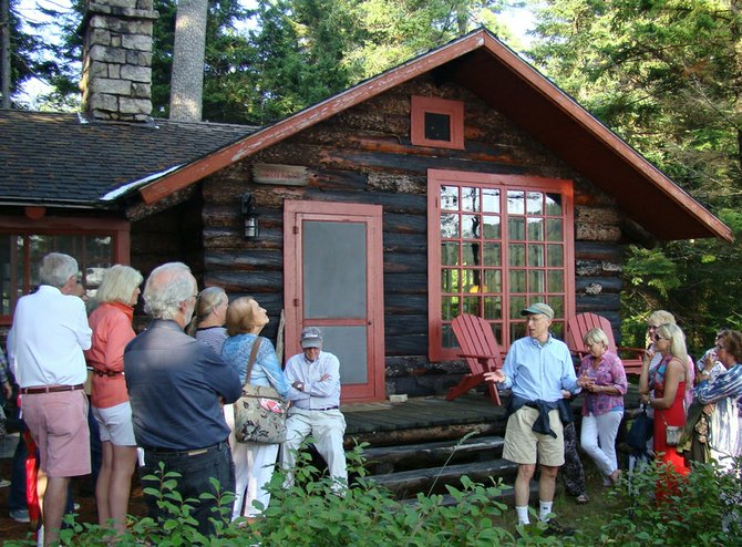 Great Arts Benefit attendees listen to Howie Kirschenbaum, one of the Great Camp Uncas owners in front of one of the many cabins on the compound.