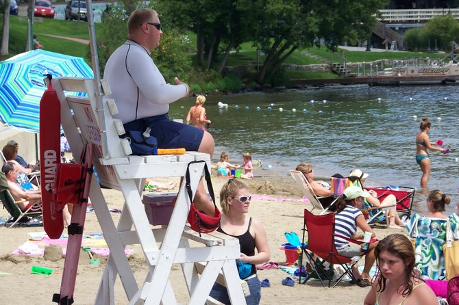 A lifeguard watches over swimmers this week at Shepard Park beach in Lake George. Although local lifeguards have monitored swimmers for decades without any major incident, the state Health Department is now requiring that the town of Lake George hire an Aquatics Director to preside over the beach activities when the youth in the town summer recreation program are swimming, athough certified lifeguards are already present.