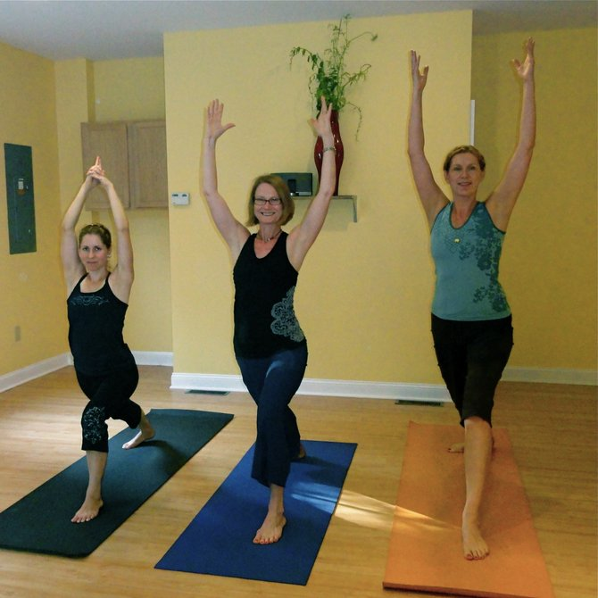 Yoga instructor Julie Lindenbaum (center), of The Yoga Studio demonstrates poses for her class. Students describe her manner as very relaxing and her classes as good workouts and just enough of a challenge. Submitted photo.