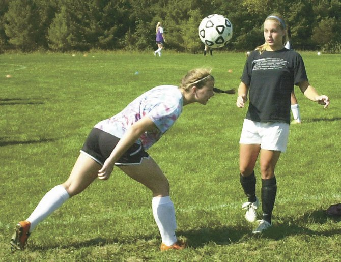 Bethlehem's Katie Nickels, left, heads the ball during the first day of girls soccer practice Monday. Nickels suffered a concussion last season.