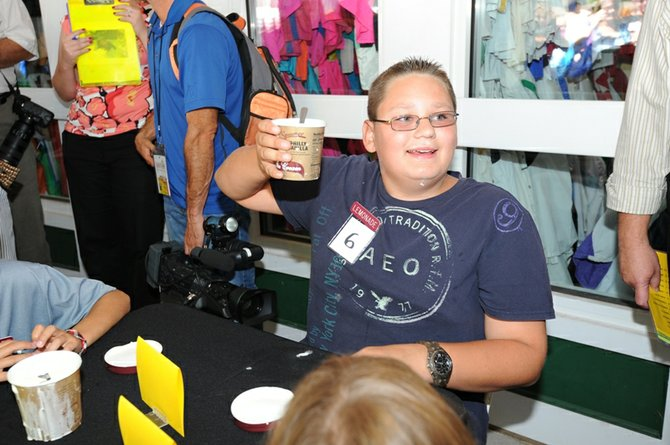 Nicholas Demitraszek, 12, of Tribes Hill, holds up his empty pint in victory after winning the kids category in the annual Stewart's Ice Cream Eating Contest at Saratoga Race Course on Wednesday, Aug. 22. Demitraszek finished his pint of Stewart's Philly Vanilla ice cream in 2 minutes and 21 seconds. Thomas Marola, 16, of Scotia, won the teen category in 50.9 seconds while Mike Nagengast, 43, of Cohoes, took the adults category at 48.9 seconds. A total of 31 track patrons participated in the annual competition.