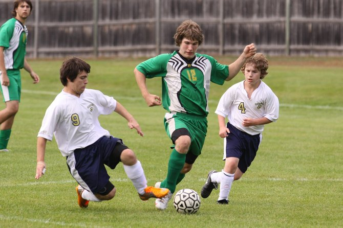 During a Sept. 2011 matchup, Warrensburg Varsity Soccer players Chris Cupp (left) and Shane Putney (right) pass the ball as a North Warren player attempts a steal. Warrensburg High School decided to shelve its soccer program for 2012 due to the resignation of a coach, not enough players to field a team, as well as budget constraints.