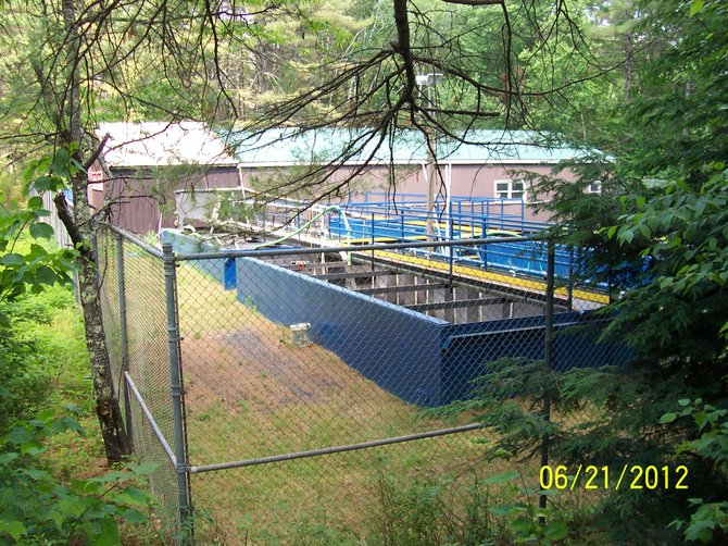 "Word of Life Institute's sewage treatment plant near the shore of Schroon Lake, photographed by Town of Chester John Wolfe on June 21, the day he was called out to investigate a noxious pool of biomass emitting a noxious smell in Schroon Lake in the vicinity of the sewer plant. Wolfe contends he saw and smelled human feces in the water; state health and environmental officials say the brown chunks were ""mats of algae,"" and that Word of Life's sewer treatment plant is working properly and in compliance with state regulations. Chester officials say they will investigate further."