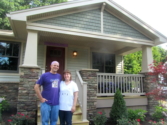Dave and Michelle Peek stand in front of their newly made over home on Kastor Avenue in Camillus.