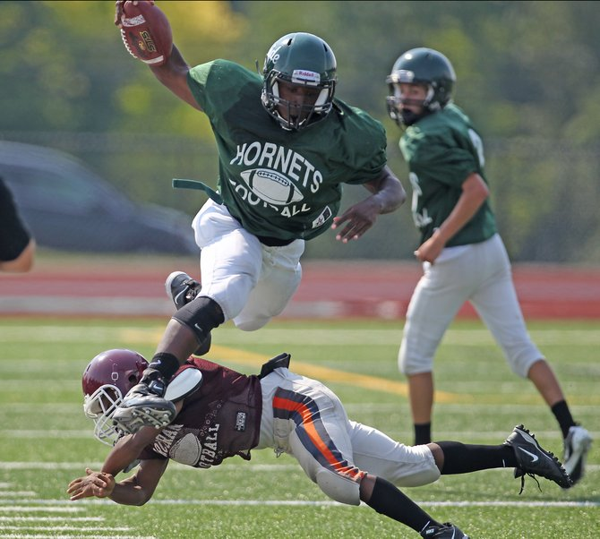 Fayetteville-Manlius freshman running back Zaire Ashley jumps down the sideline versus Corcoran during a scrimmage Saturday, Aug. 25, at F-M High School.